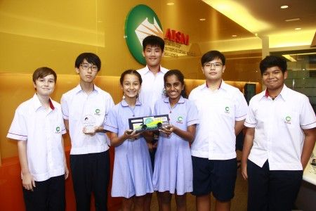 One of AISM's winning teams posing with their trophy and Formula 1 Car Model.