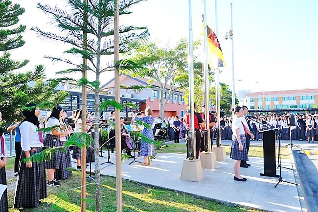 JIS Orchestra plays the national anthem as the flag is raised for 36th National Day celebration